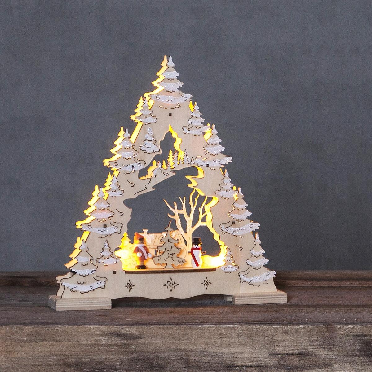 Elljusstake i laserutskuret trä i form av en gran med tomte och snögubbe framför hus