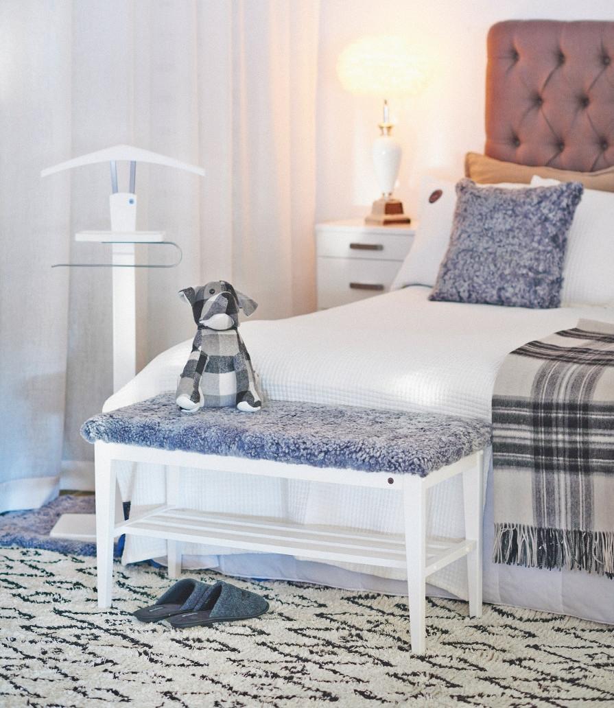 Sovrumsmöbler med sittbänk med fårskinn. Vitt sovrum med trämöbler.